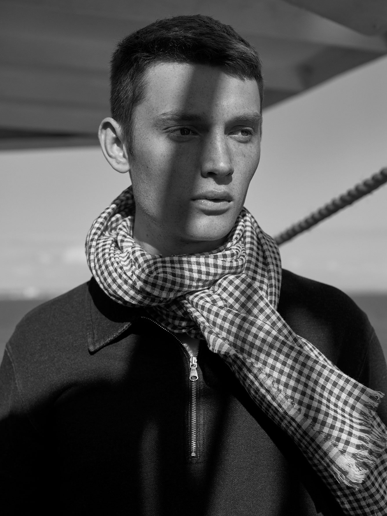 Black and white photo of male model wearing black and white gingham scarf