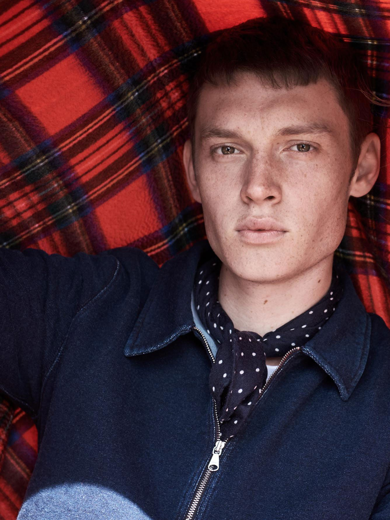Male Model Wearing a navy neckerchief with white spots and a navy sports code holding a red tartan blanket behind him