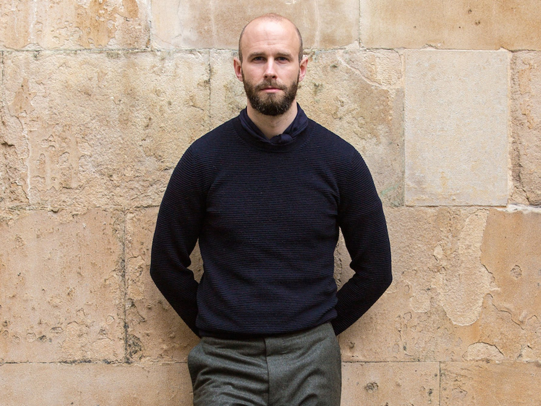 Simon Crompton leans against a brick wall wearing a navy jumper with navy cashmere square neckerchief and grey slacks